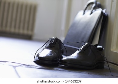 Closeup of formal shoes and briefcase on floor