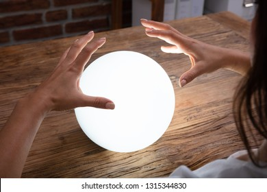 Close-up Of Fortuneteller's Hand Covering The Glowing Crystal Ball On Desk