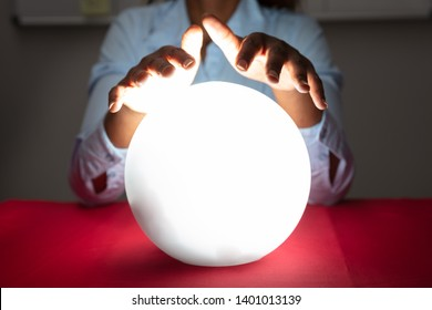 Close-up Of Fortuneteller's Hand Covering The Glowing Crystal Ball On Red Desk