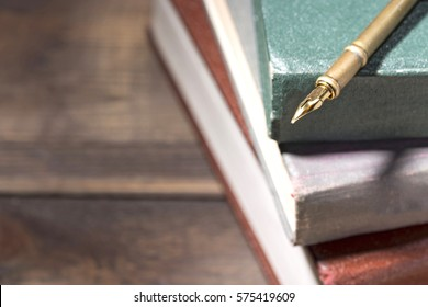 Closeup of fountain pen on stack of old books. Selective focus