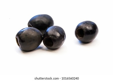 Closeup of Four Black Olives on a White Background
