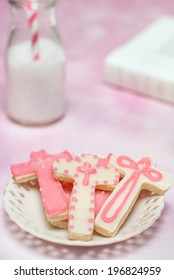 Close-up Four (cross shaped) pink cookies on plate with milk bottle and bible