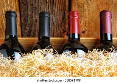 Closeup of four different wine bottles in a wooden crate with straw packing material.