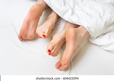 Close-up of four feet in a bed under the white blanket