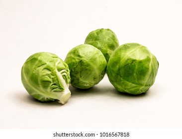 Closeup of Four Fresh Green Brussels Sprouts on a white background