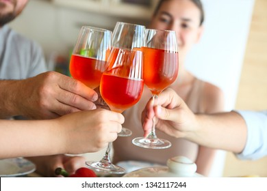 Closeup of four glasses with rose wine being clinked together during a toast at a celebration