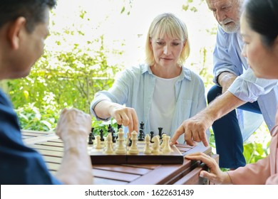 Closeup four multiethnic senior people wearing casual dressed sitting at house, playing chess board and having fun together. Elder caucasian husband man teaching caucasian wife woman how to play.