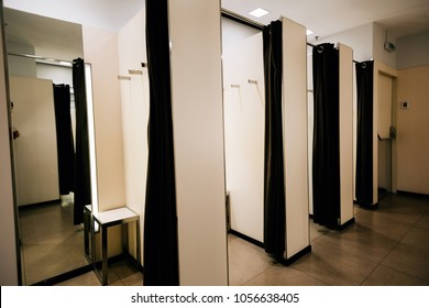 Closeup of four opened fitting rooms and  with no people inside.
