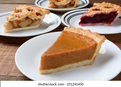 Closeup of four slices of pie on dessert plates. Focus is on the front slice. The back plates have apple and cherry. Horizontal format on an old wood kitchen table.