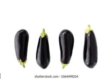 Closeup of four whole aubergines with water drops on white background.