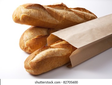 The closeup of french baguette in the paper bag isolated on white.