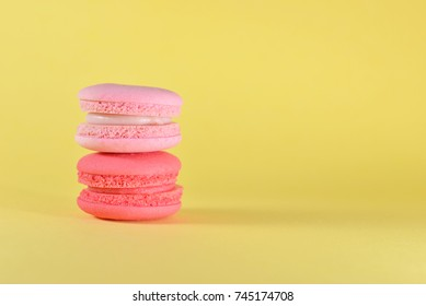 Closeup of French colourful macarons on yellow background. Colorful creative concept with copy space for design works. Sweet dessert for relaxing time. Idea for wallpaper and beautiful greeting card.
