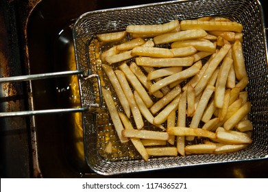 Close-up of french fries in boiling oil