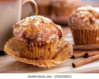 Closeup of a french toast muffin with cinnamon sticks on a wooden surface with muffins and coffee cup in background