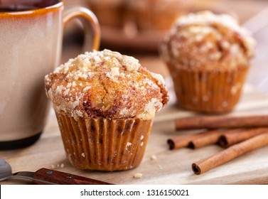 Closeup of a french toast muffin with cinnamon sticks and cup of coffee on a wooden surface with muffins in background