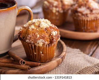 Closeup of a french toast muffin with cinnamon sticks and cup of coffee on a wooden plate with muffins in background