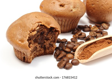 Closeup of fresh baked coffee muffins, coffee grains and powdery cinnamon on wooden spoon, bitten muffin. Isolated on white background