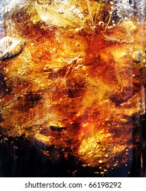 Closeup of fresh brown splashing liquid - cola or other drink with ice and air bubbles