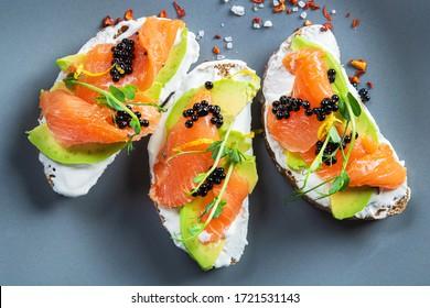 Closeup of fresh bruschetta avocado salmon and black caviar. Diet morning food background. Top view.