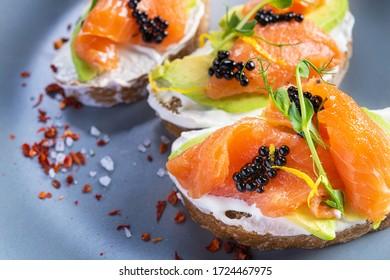 Closeup of fresh bruschetta avocado salmon and black caviar. Diet morning food background.