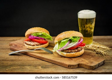 Closeup of fresh burger and a cold beer on wooden