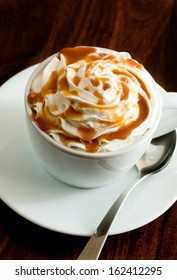 closeup of a fresh caramel latte with whipped cream