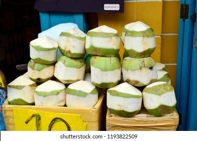 Closeup of fresh coconut fruit for sell on a yellow plastic box with ice on street in Bangkok, Thailand. Food, healthy and street food concept.