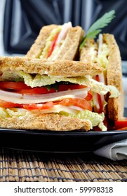 closeup fresh and delicious classic club sandwich over a black glass dish with coffee and toasters