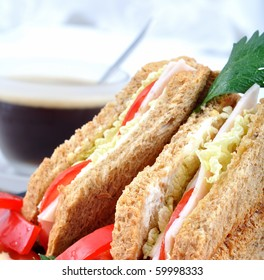 closeup fresh and delicious classic club sandwich over a black glass dish with coffee and vegetable