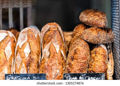 Closeup of fresh golden traditional baked Italian bread loaves in bakery basket wooden with sign in Florence Italy Firenze Centrale Mercato central market