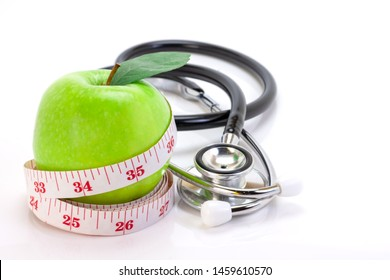 Closeup fresh green apple fruits  with measuring tape and medical stethoscope isolated on white background. Slim diet and eating for healthy ,anti-aging conceptual. Space for text.