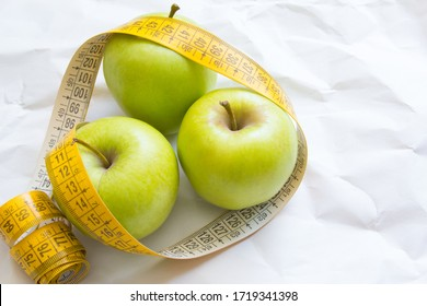 Closeup fresh green apples fruits with measuring tape isolated on white background. Slim diet and eating for healthy. Alkaline diet.