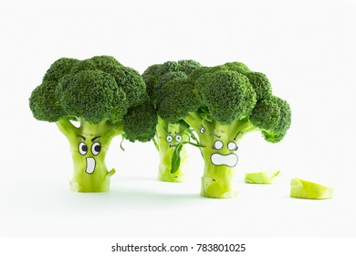 Closeup of fresh green broccoli with scared cartoon style faces on white background