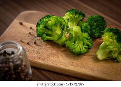Nahaufnahme von frisch grüne Brokkolis auf einem hölzernem Brett, gewürzt und gekocht mit Holztisch und Glaspfefferbehälter