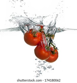 Closeup of fresh and health tomatoes falling into clear water with big splash isolated on white background. Clean eating diet concept