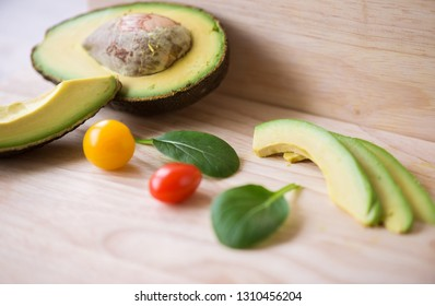 Close-up of a fresh juicy green ripe avocado on wooden table. Healthy food concept.