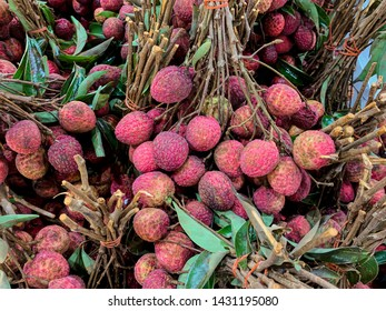 Closeup fresh Lychees (Litchi Chinensis) with stew and leaves. Sweet tasty tropical fruit.