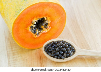 Closeup of fresh papaya seeds next to cut papaya fruit showing orange texture