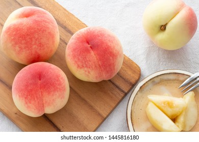 Close-up of a fresh peach placed on a white cloth.