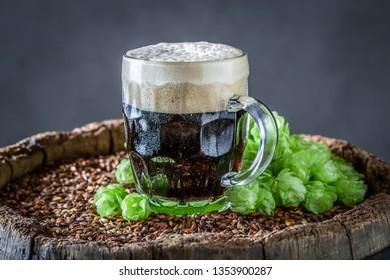Closeup of fresh pint of dark beer with white foam