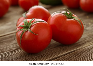 Close-up of fresh, ripe tomatoes on wood background
