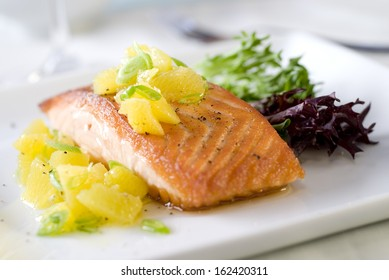 Closeup of a fresh salmon fillet with a juicy orange relish.