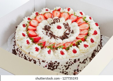 Closeup of a fresh strawberry cake with sliced strawberries and chocolate in a box