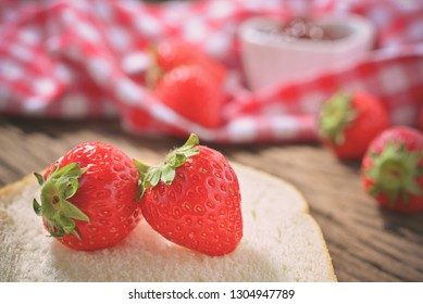 Closeup of fresh strawberry on bread with strawberry jam in love ceramic cup with wooden background. Selective focus for designed works.Concept about homemade cooking with love.Vintage Style.