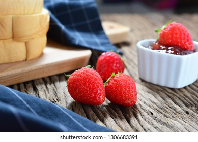 Closeup of fresh strawberry on bread with strawberry jam in love ceramic cup with wooden background. Selective focus for designed works.Concept about homemade cooking with love.