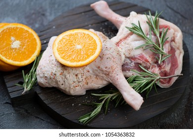 Close-up of fresh uncooked duck legs with condiments on a black wooden chopping board, studio shot, selective focus