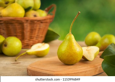close-up of a fresh yellow pear on a wooden table in the background of a basket with pears and pears.