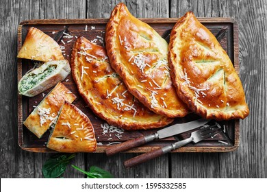 close-up of freshly baked Calzones, closed pizzas with Spinach and Cheese filling sprinkled with grated parmesan on a rude wooden board on a rustic wooden table, italian cuisine, flatlay