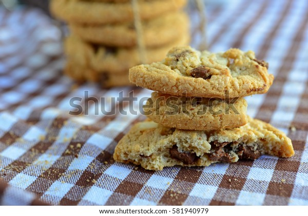 Closeup of freshly baked chocolate chip cookies on brown napkin. Stacked homemade cookies.