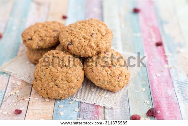 Closeup of freshly baked cranberry oatmeal cookies on colorful background